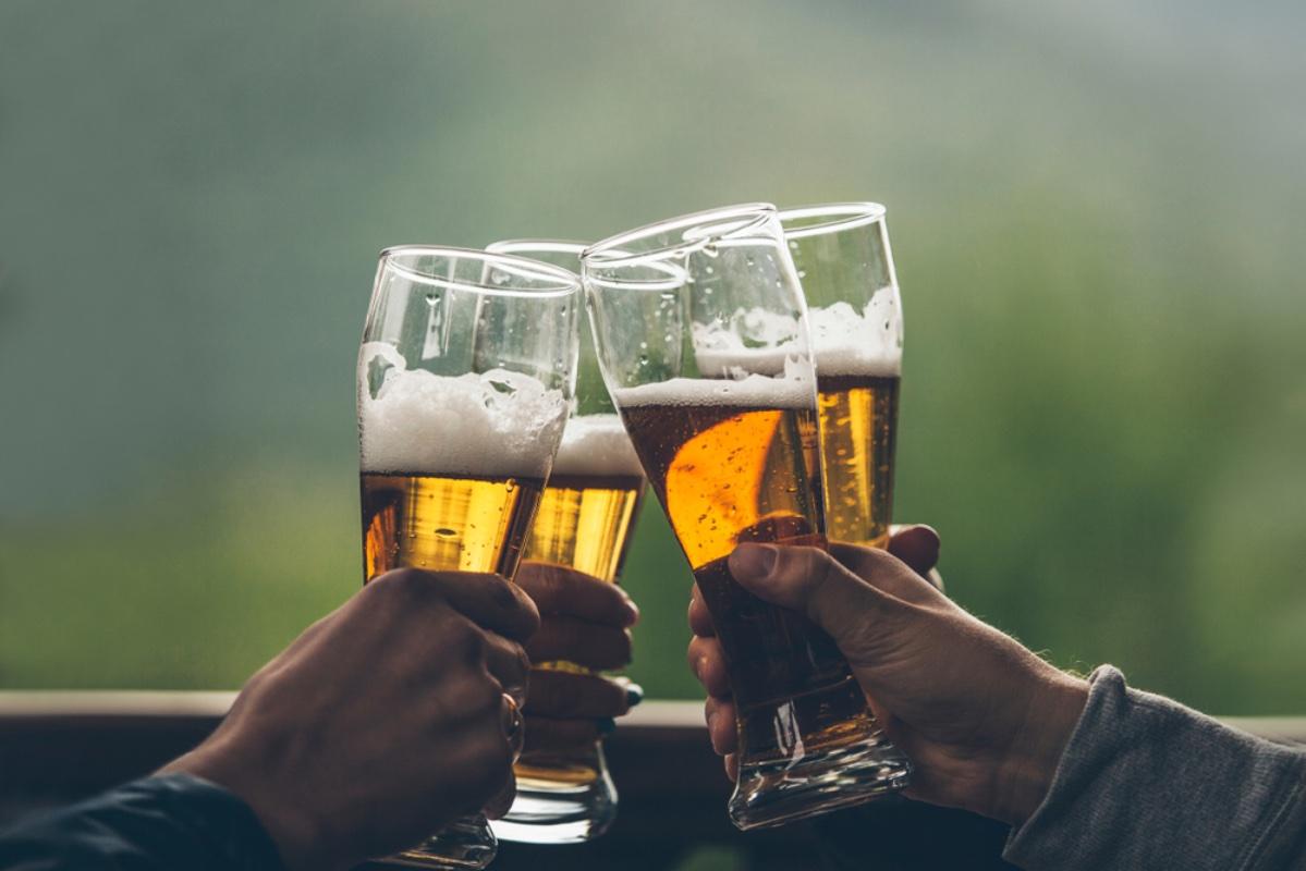 Birra con schiuma luce ragazzi alti nelle mani di amici alzando un primo piano brindisi